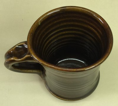 A porcelain mug warps under the weight of its own handle